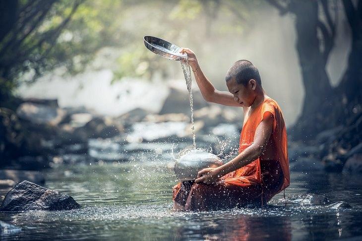 נזיר בודהיסטי יושב בנהר ושופך על אבן שעליו מים מקערה