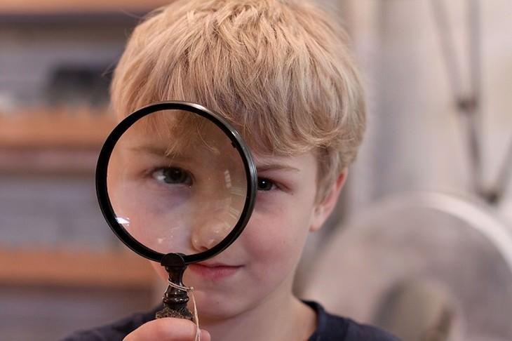 ילד משתמש בזכוכית מגדלת