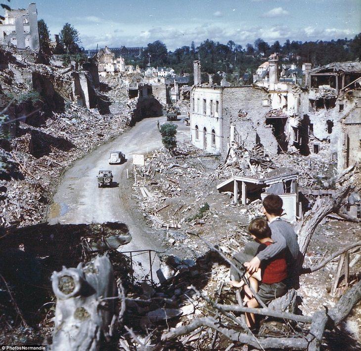 היום שאחרי הפלישה הגדולה לנורמנדי, שני נערים מביטים על חיילים אמריקאים בעיר סן-לו. צרפת 1944.