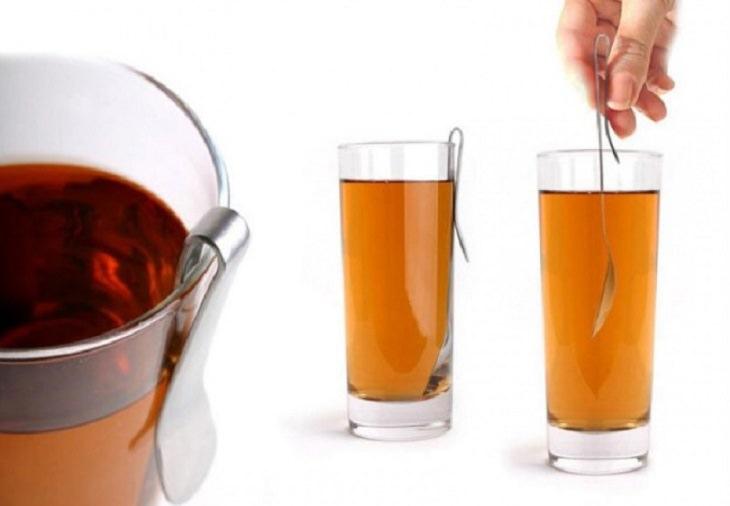כפית עם קליפס מוצמדת לדפנות כוס זכוכית שקופה