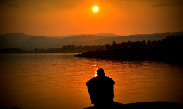 איש יושב על שפת אגם ומביט בשקיעה