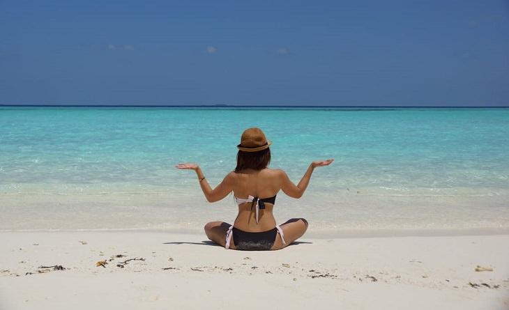 אישה יושבת על חוף ים