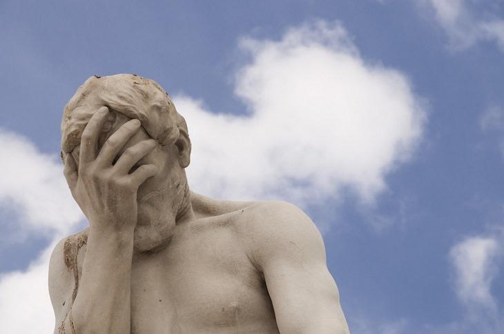 פסל שיש של איש תופס את ראשו