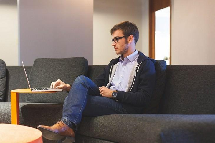 אדם יושב בהצלבת רגליים מול מחשב
