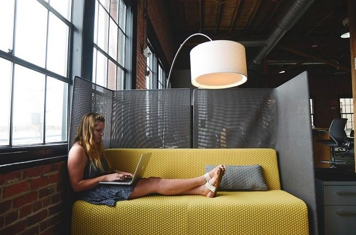 אישה יושבת על ספה עם מחשב נייד בחיקה