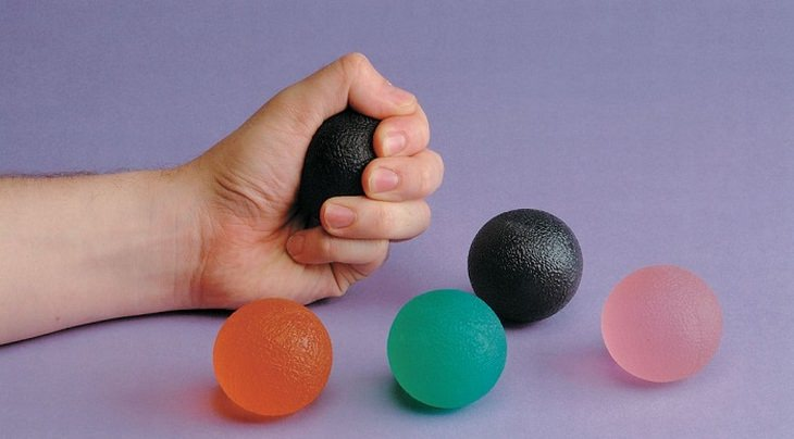 יד לוחצת כדור גומי בתוכה, ולצדה עוד מספר כדורי גומי צבעוניים