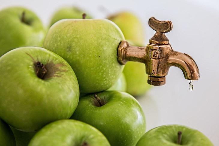 שימושים יעילים בתפוחי עץ ובחומץ תפוחי עץ: תפוחי עץ ירוקים מחוברים לברז מתכת