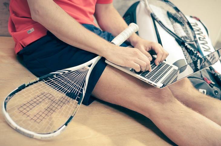 ילד עם מחבט טניס עליו משתמש בלפטופ