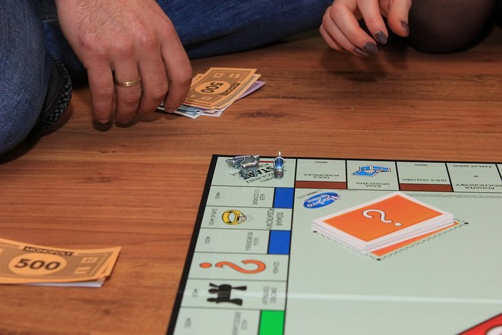 משחק קופסה מונח על הרצפה עם שני אנשים משחקים לצידו