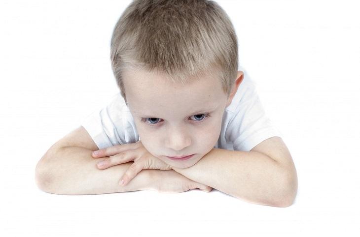 ילד שמניח את ראשו על ידיו המשולבות