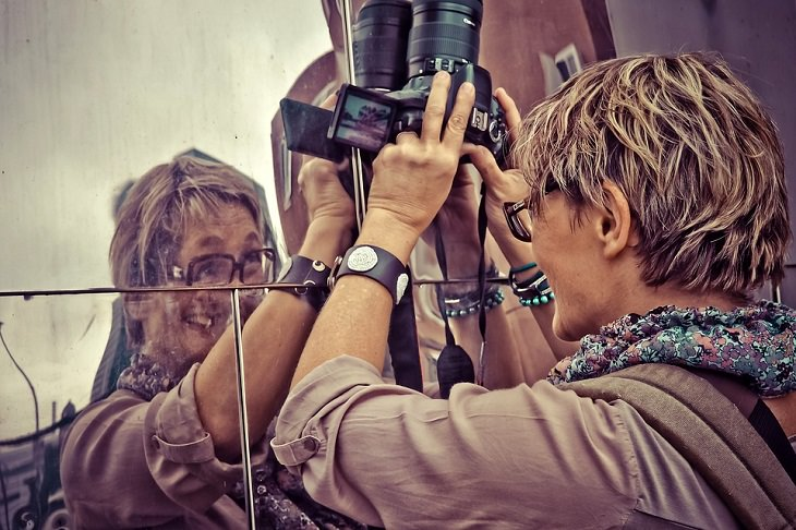 אישה מצלמת את דמותה מול חלקי מראה