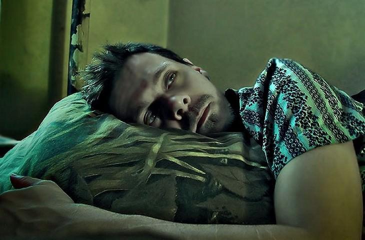 גבר שלא מצליח להירדם עם ראשו על הכר