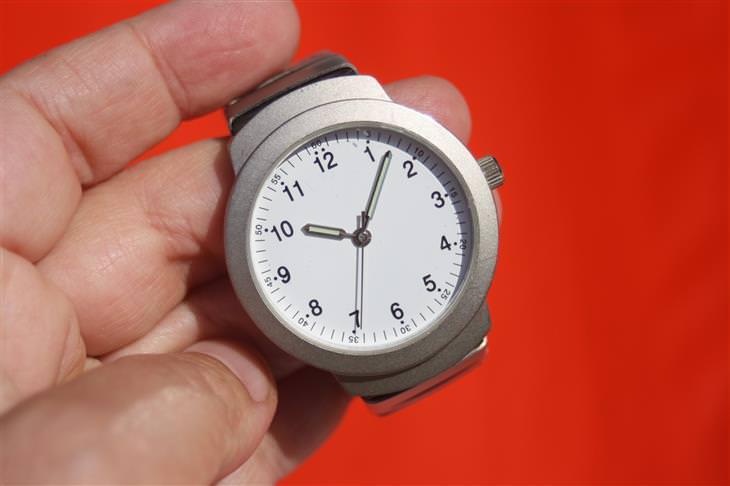 יד אוחזת בשעון על רקע אדום