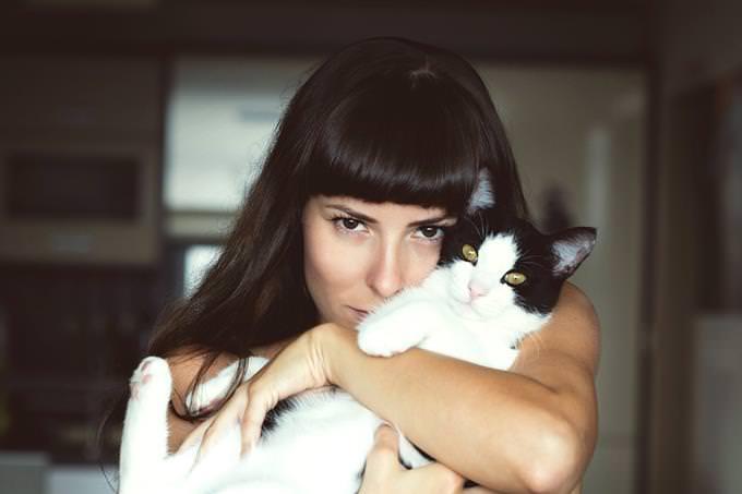 אישה מחבקת חתול בחוזקה