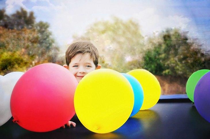 ילד מוקף בלונים צבעוניים