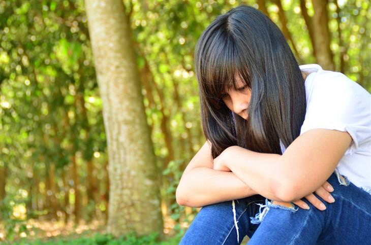 אישה יושבת ביער, מחבקת את רגליה ומרכינה את ראשה