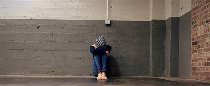 גבר יושב על הרצפה, מחבק את רגליו ומרכין את ראשו