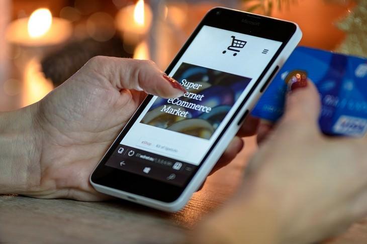 יד של אישה מחזיקה כרטיס אחת כשהיד השנייה מחזיקה טלפון נייד