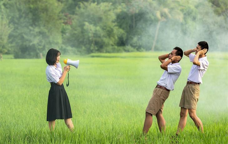 אישה צועקת במגפון על שני גברים
