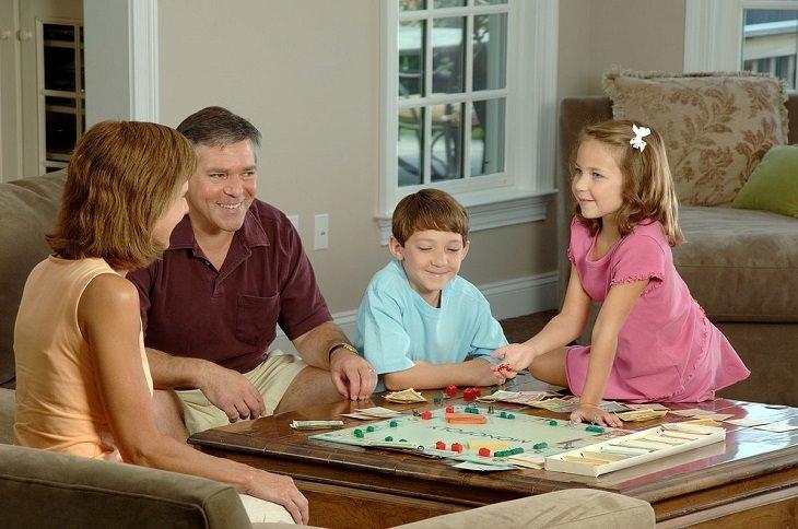 הצעות למשחקי חברה: משפחה משחקת משחק לוח סביב השולחן בסלון