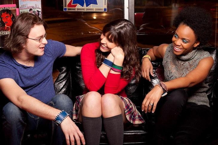 הצעות למשחקי חברה: שתי נשים וגבר מחייכים בבילוי על ספה