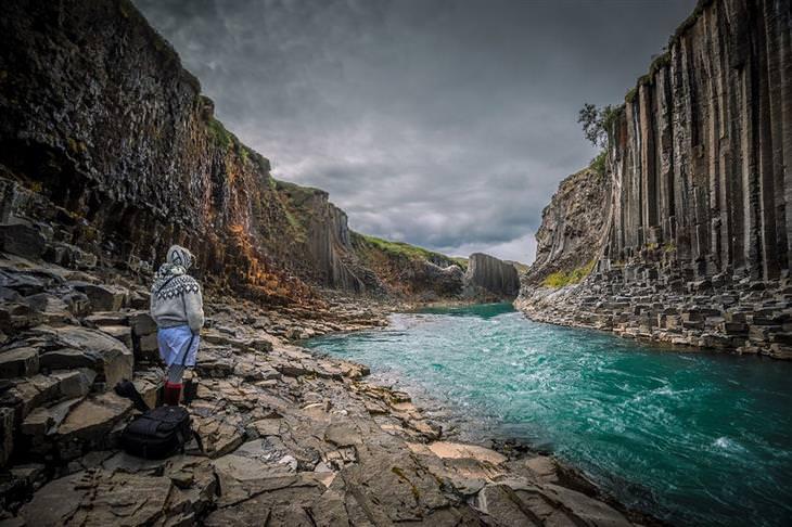 אישה עומדת מול הרים ונהר