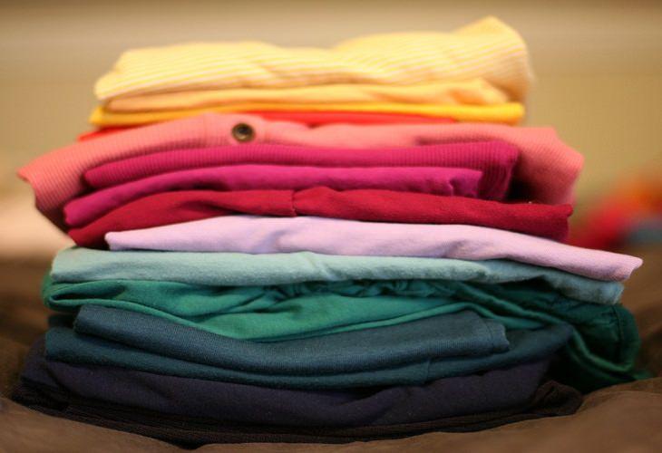 מדריך לקיפול נכון ויעיל של בגדים: חולצות מקופלות מונחות אחת על השנייה