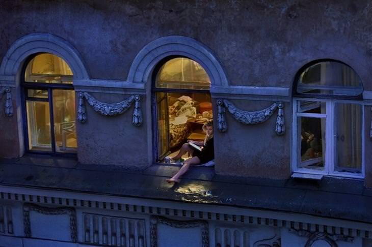אישה יושבת על אדן החלון וקוראת ספר