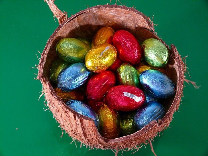 ביצי שוקולד עטופות מונחות בתוך קליפת קוקוס