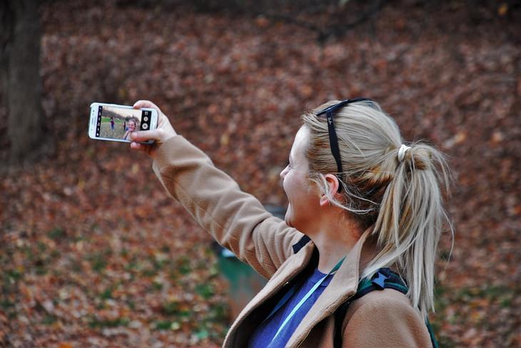 אישה מצלמת את עצמה באמצע יער
