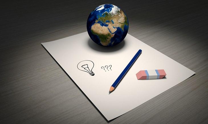 עיפרון על דף נייר ריק, עם מחק ודגם של כדור הארץ