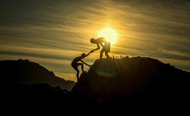 צללית ילד עוזר לילד אחר לטפס על הר