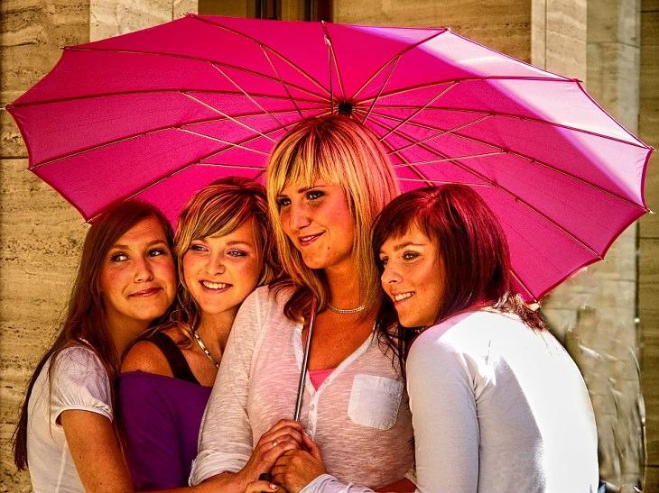ארבע נשים תחת מטריה ורודה