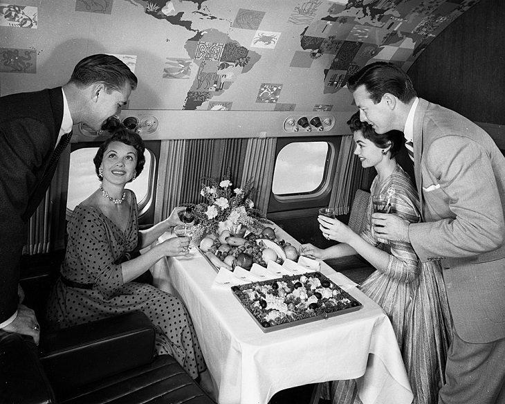 שני זוגות נהנים מאוכל ושתיה על מטוס