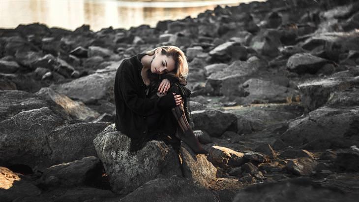 אישה יושבת על סלעים ומחבקת את רגליה