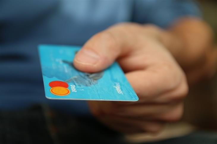 יד של גבר מגישה כרטיס אשראי