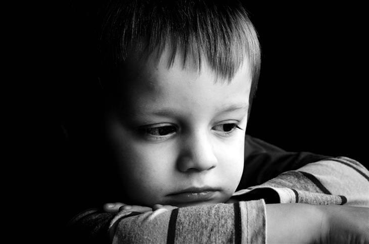 ילד עם ידיים משולבות וראש רכון עליהן
