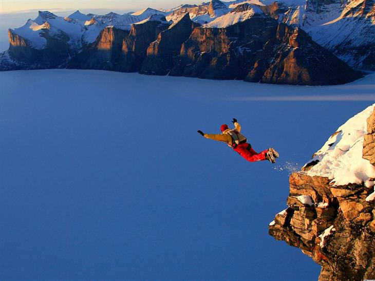 אדם קופץ מצוק לצניחה מול נוף הררי מושלג