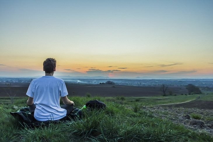 אדם יושב על דשא מול נוף טבעי