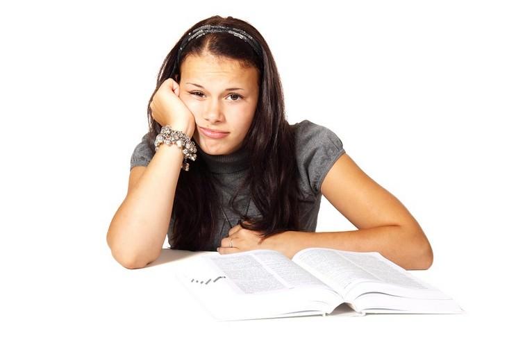 אישה עם מבט מיואשת  מניחה את ידה על ספר