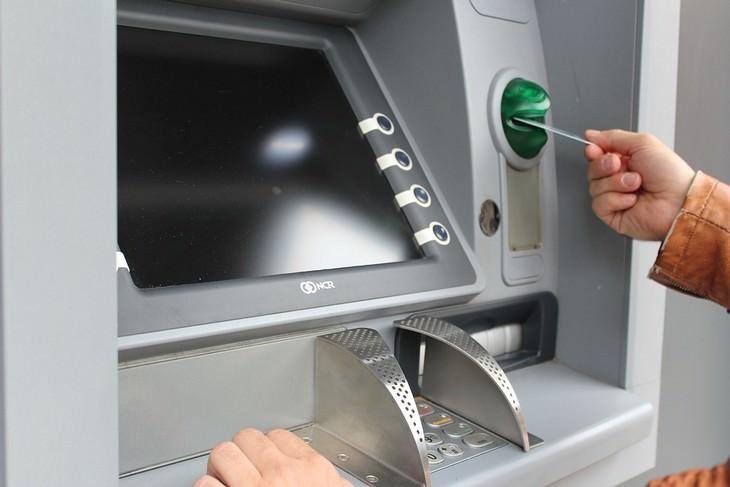 יד של גבר מכניסה כרטיס אשראי לכספומט