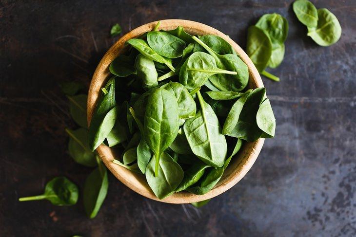 מזונות על להורדת המשקל: עלי תרד מונחים בקערה על שיש