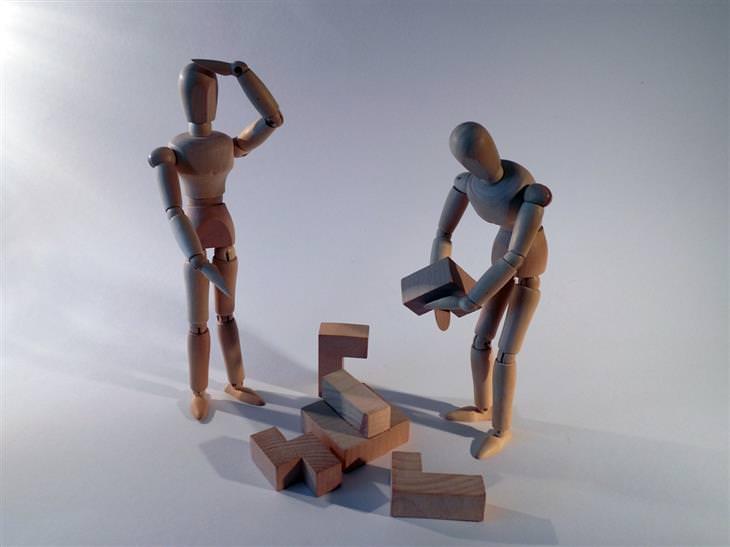 שתי בובות מעץ מנסות לפתור פאזל תלת ממדי