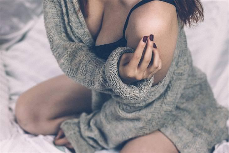 אישה יושבת על מיטה ומלטפת את הכתף שלה