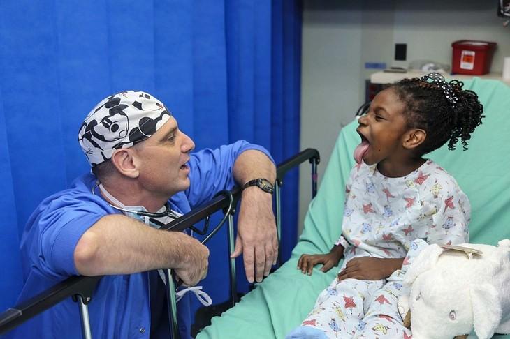 ילדה יושבת על מיטת בית חולים ומוציאה לשון לרופא שכורע מולה