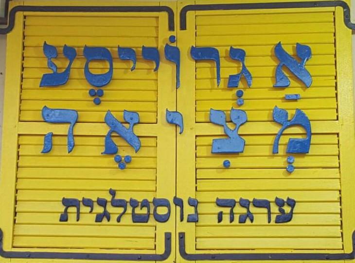 שלט עץ בפתח שעליו כתוב א גרויסע מציאה