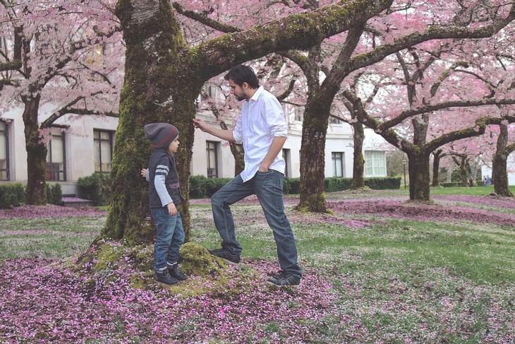 אב ובן משוחחים לצד עץ