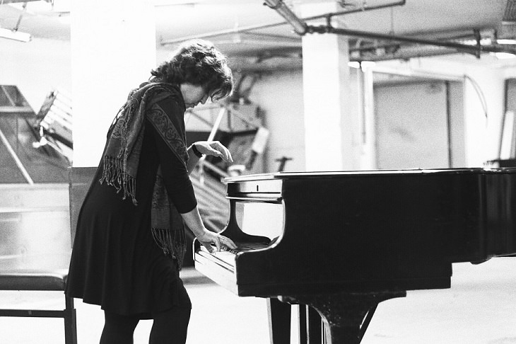 אישה עומדת מנגנת על פסנתר