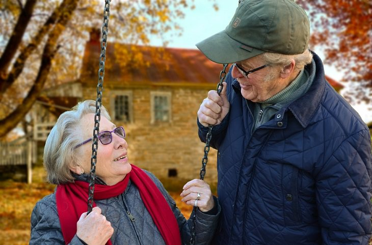 אישה מבוגרת מתנדנדת בנדנדה בחצר הבית, בן זוגה צופה בה לידה