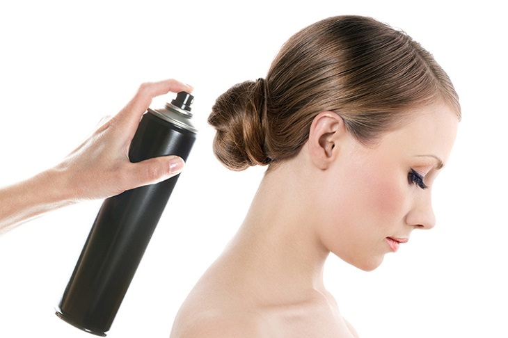 ריסוס ספריי לשיער על שיערה של בחורה